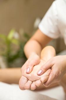 Woman receiving foot massage in spa salon