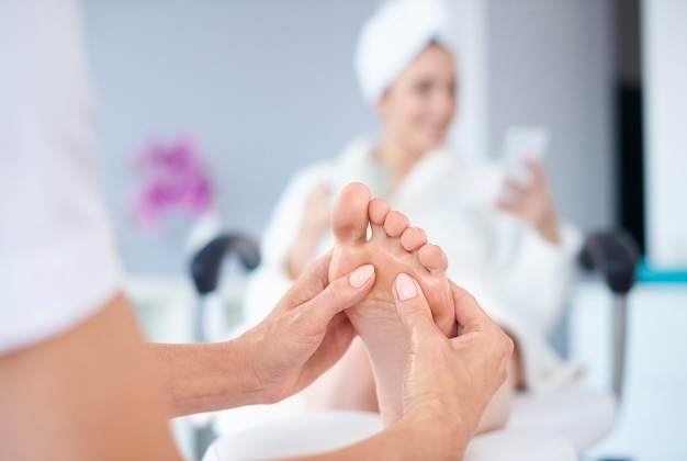 Woman receiving foot massage in spa