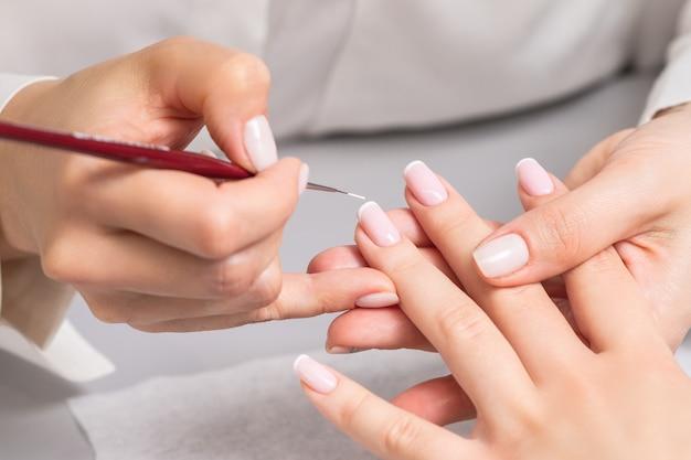 Женщина получает французский маникюр косметологом