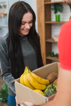 Woman receiving fruits with courier
