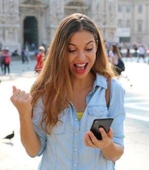 Женщина получает хорошие новости онлайн в смартфоне на улице