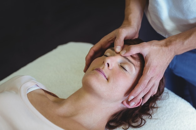 Woman receiving head massage from physiotherapist