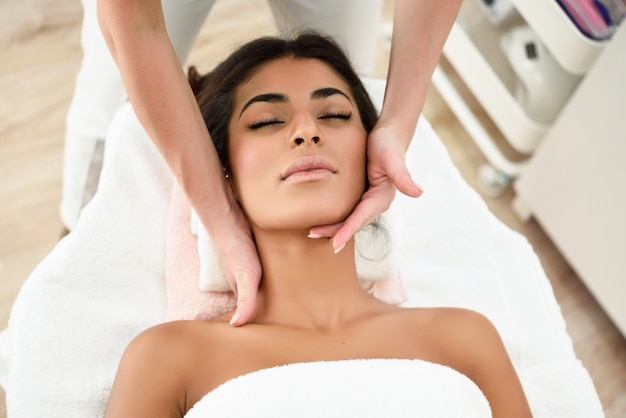 Woman receiving head massage in spa wellness center.