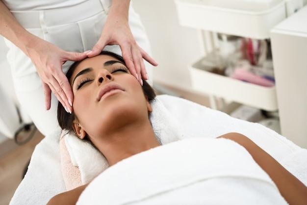 Woman receiving head massage in spa wellness center.