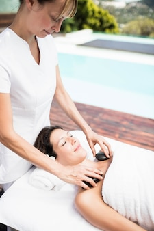 Woman receiving a hot stone massage from masseur in a spa