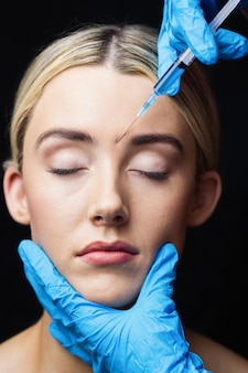 Woman receiving injection on her forehead