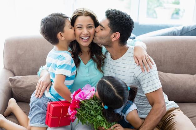リビングルームで彼の夫と子供からキスを受け取る女性