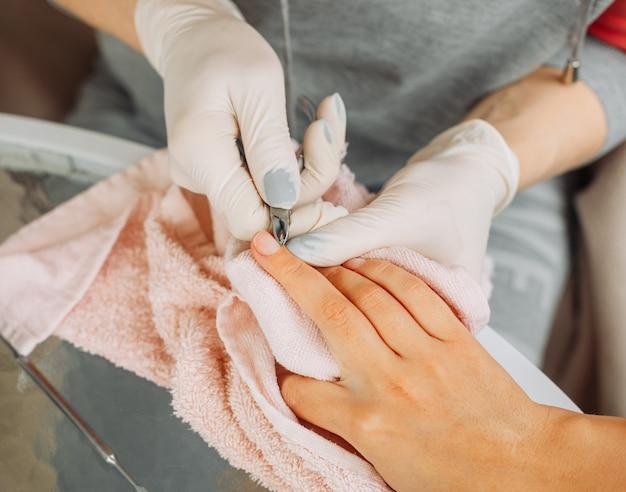 Una donna che riceve manicure da una donna in guanti e maschera nel salone di bellezza durante il giorno