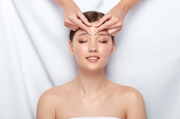 Woman receiving massage for her forehead with smile on face