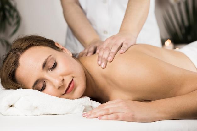 Женщина получает массаж в спа-центре
