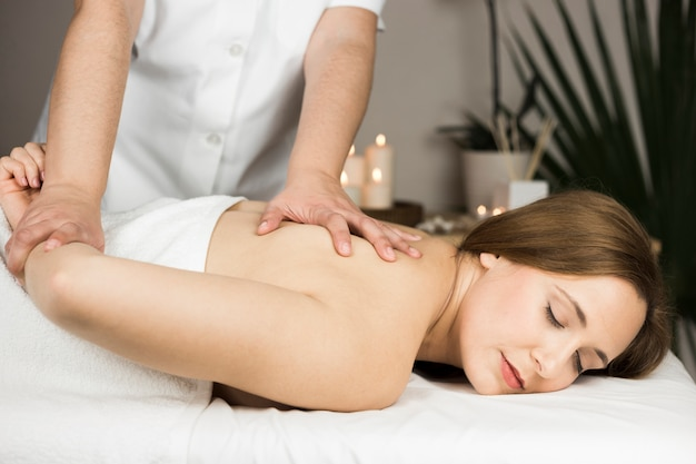 Woman receiving massage in spa center