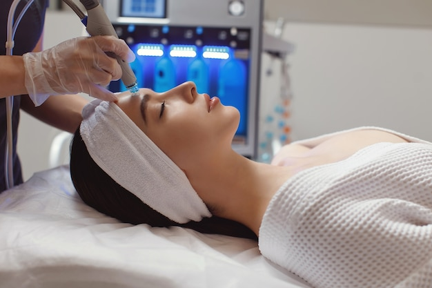 Woman receiving microdermabrasion therapy on forehead at beauty spa
