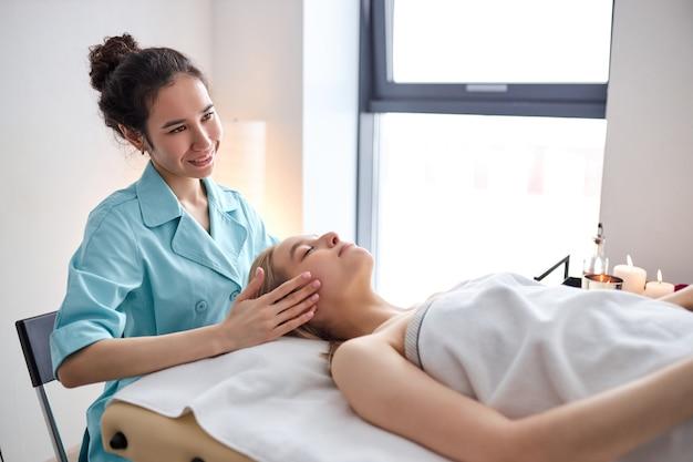 여성의 클리닉 측면에서 얼굴과 머리에 정골 또는 카이로프랙틱 치료를 받는 여성...
