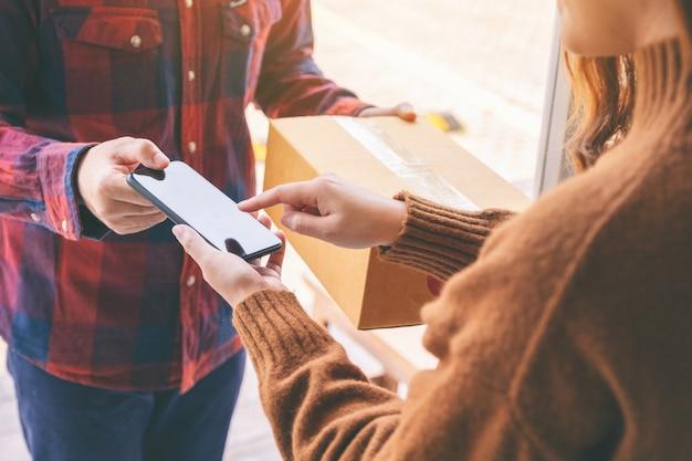 집 문 앞에 있는 배달원에게서 전화로 소포 상자를 받고 이름에 서명하는 여성