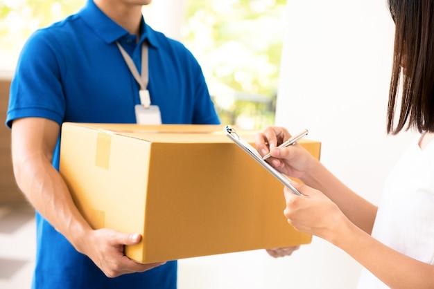 配達人から小包を受け取っている女性