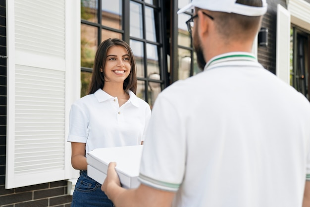 Woman receiving pizza from courier