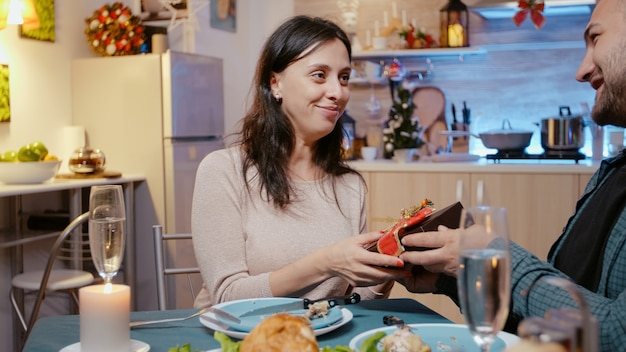 Woman receiving present box from man at festive dinner