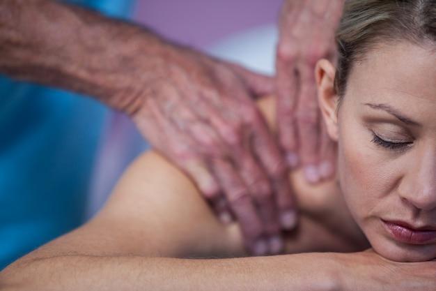 理学療法士から肩のマッサージを受ける女性