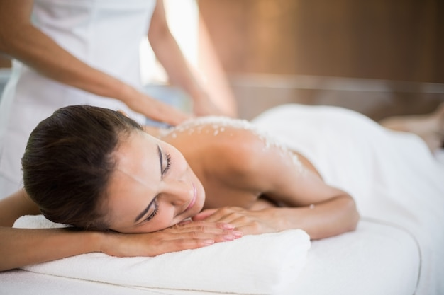Woman receiving spa treatment from female masseur