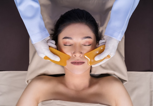 Woman receiving traditional guasa face therapy