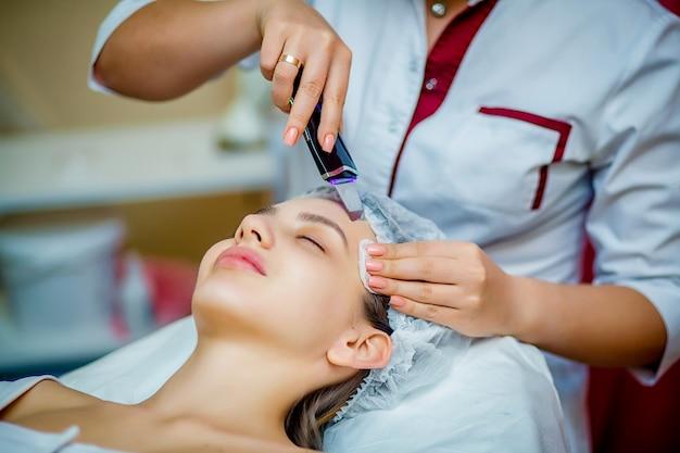 Woman receiving ultrasonic facial exfoliation at cosmetology salon.