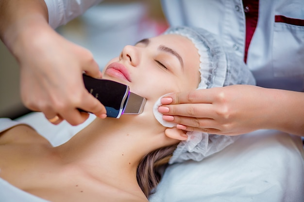 Woman receiving ultrasonic facial exfoliation at cosmetology salon