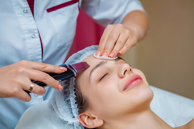 Woman receiving ultrasonic facial exfoliation at cosmetology salon.