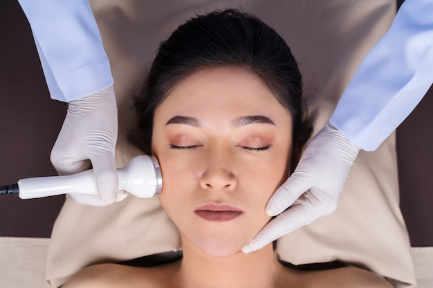 Woman receiving ultrasound facial beauty treatment skin care