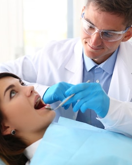 Woman at the reception of a male dentist examining teeth