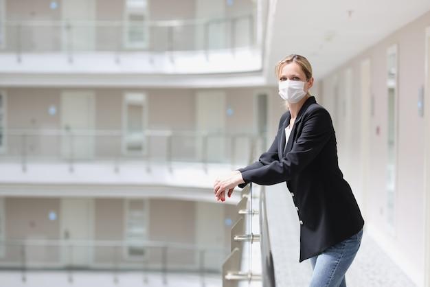 의료 보호 마스크의 여성 접수는 호텔 단지의 복도에 서