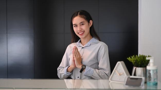 Портье женщина сидит за стойкой регистрации и поднимает руки в знак почтения приветствовать посетителей в отеле.