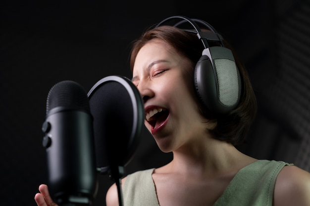 Женщина записывает песню или рассказывает истории в студии