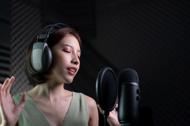 スタジオで歌や物語を録音する女性。