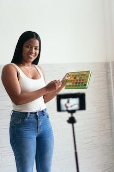 自宅でビデオカメラを使ってビデオvlogを録画している女性