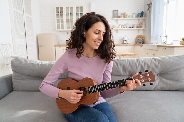 Женщина записывает контент в видеоблог, играет на гитаре укулеле и смотрит на веб-камеру во время изоляции дома