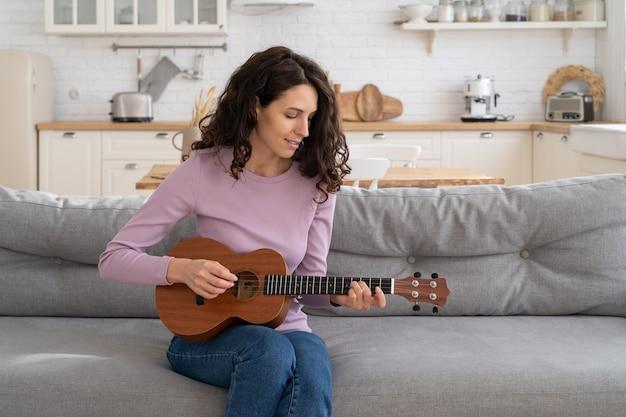 Женщина записывает контент для видеоблога, играя на гитаре укулеле