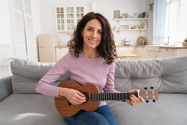 Woman recording content to vlog, playing on ukulele guitar looking at webcam during lockdown at home