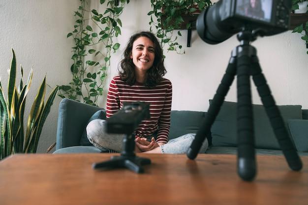 카메라를 보며 웃고 있는 vlog를 위해 집에서 자신을 녹화하는 여자 비디오 블로깅에 대한 선택적 초점