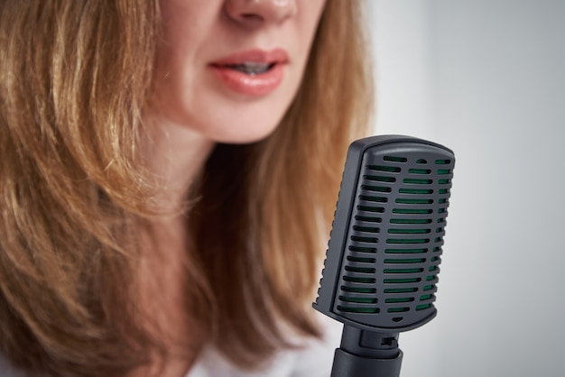 Woman recording online podcast at home, podcasting concept