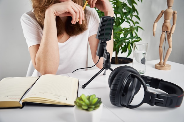 Woman recording online podcast at home