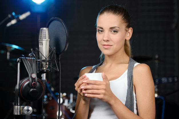 Woman recording a song in a professional studio.
