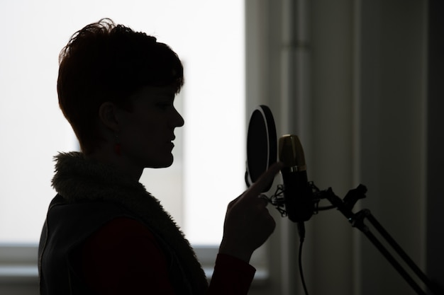 Woman in recording studio recording singing and speaking for processing and using for film and video