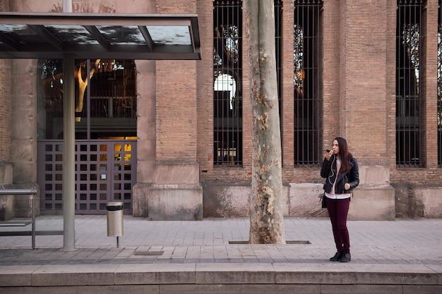 거리에서 음성 메시지를 녹음하는 여자