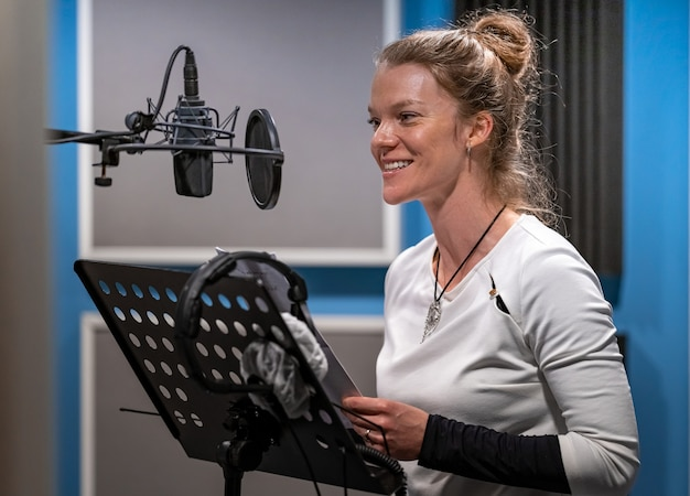 Woman recording voice speech voiceover and singing in studio