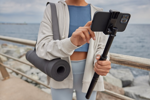 Woman records video for blog or makes selfie holds smartphone on stick dressed in tracksuit carries fitness mat stands near sea against beautiful nature view