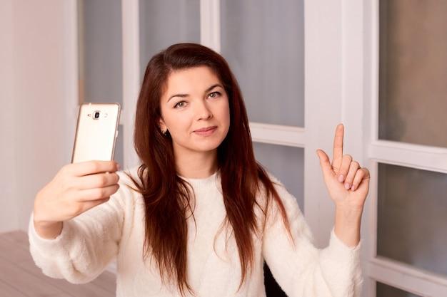 여자는 새 건물이나 집에서 카메라 폰에 비디오 인사말을 기록합니다.