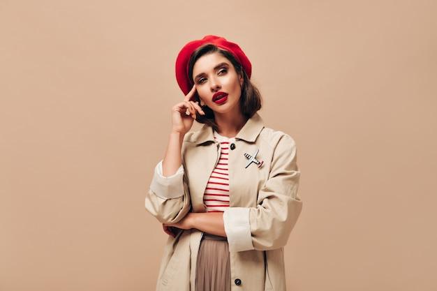 Donna in berretto rosso e cappotto minuziosamente in posa su sfondo beige. signora moderna con rossetto luminoso in maglione a righe e mantello alla moda distoglie lo sguardo.