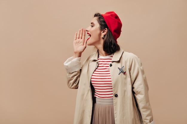 Donna in berretto rosso e trincea grida su sfondo beige. ragazza alla moda con labbra luminose in maglione a righe e pose cappotto alla moda per la fotocamera.
