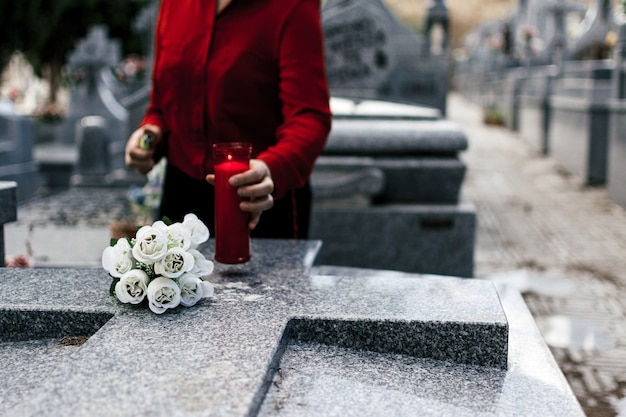 Woman in red blouse lighting a candle and putting flowers to a loved one in the cemetery.