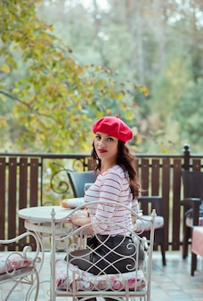 Woman in a red cap drinking red wine in outdoor cafe